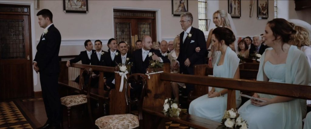 groom waits at top of aisle for bride and father