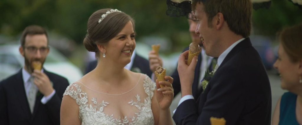 bride and groom share ice cream