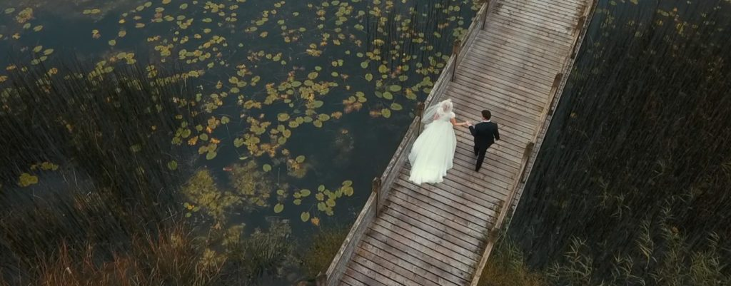 boardwalk bride path over lake pond and waterlilys with bride and groom