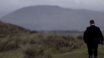 bride groom walk sand dunes sligo with mountains dress suit